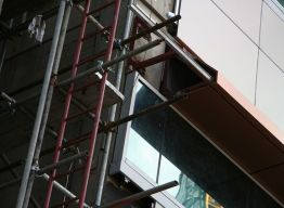 Scaffolding at corner for workers to seal panel joints
